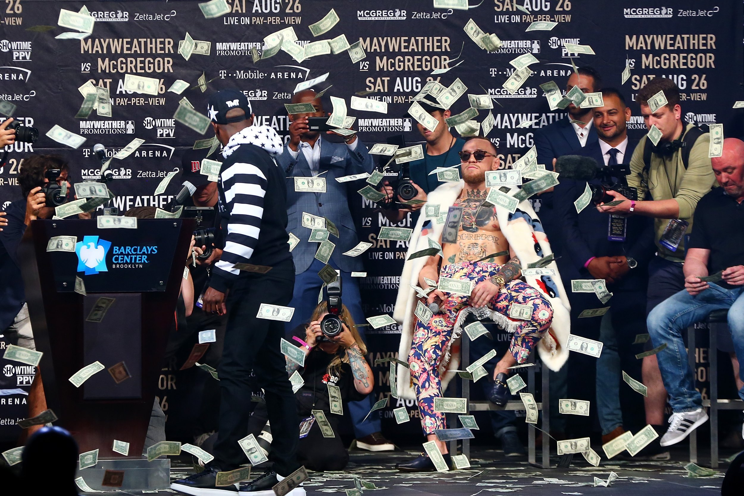 Floyd Mayweather Jr. looks on as money rains down on Conor McGregor in Brooklyn, New York City, July 13.