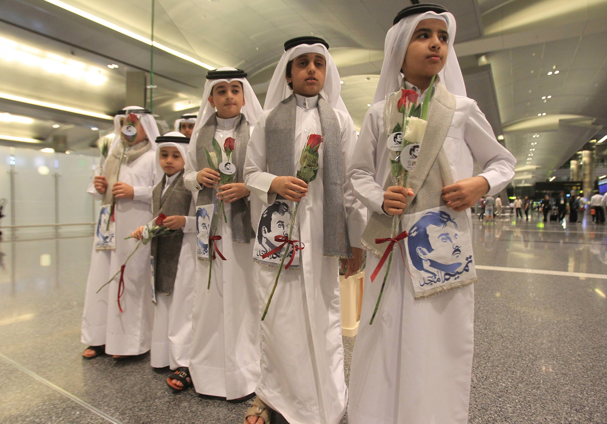 Qatari children hold flowers and pictures of Qatar Emir Sheikh Tamim Bin Hamad Al-Thani