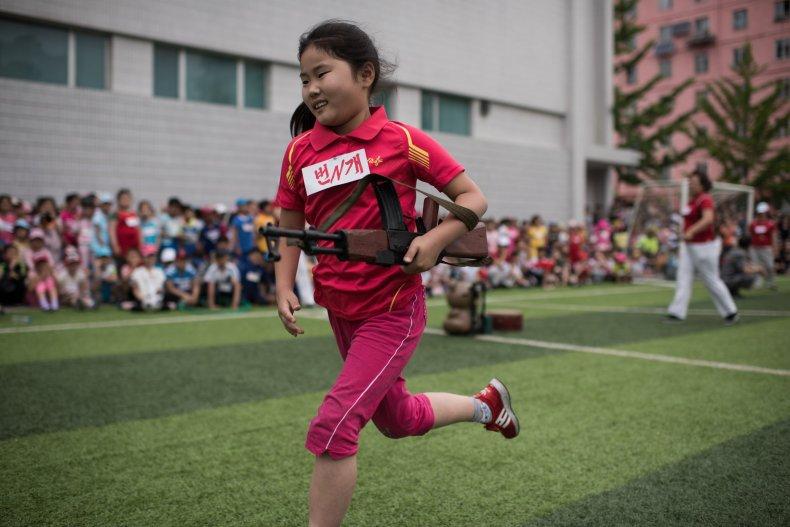 North Korean child carrying mock rifle
