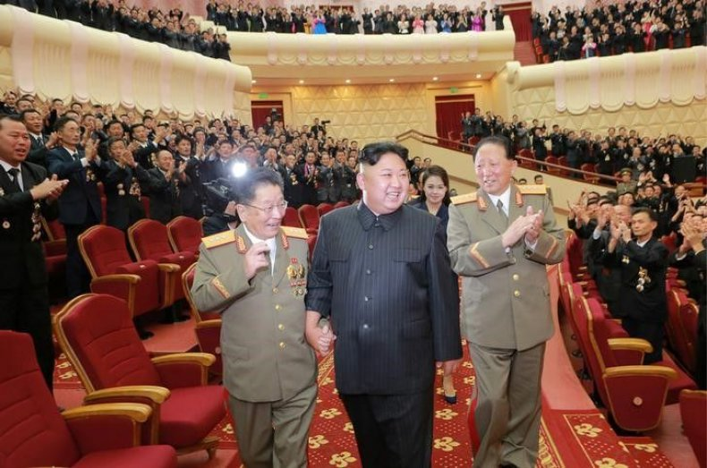 Kim Jong Un holds hands with official