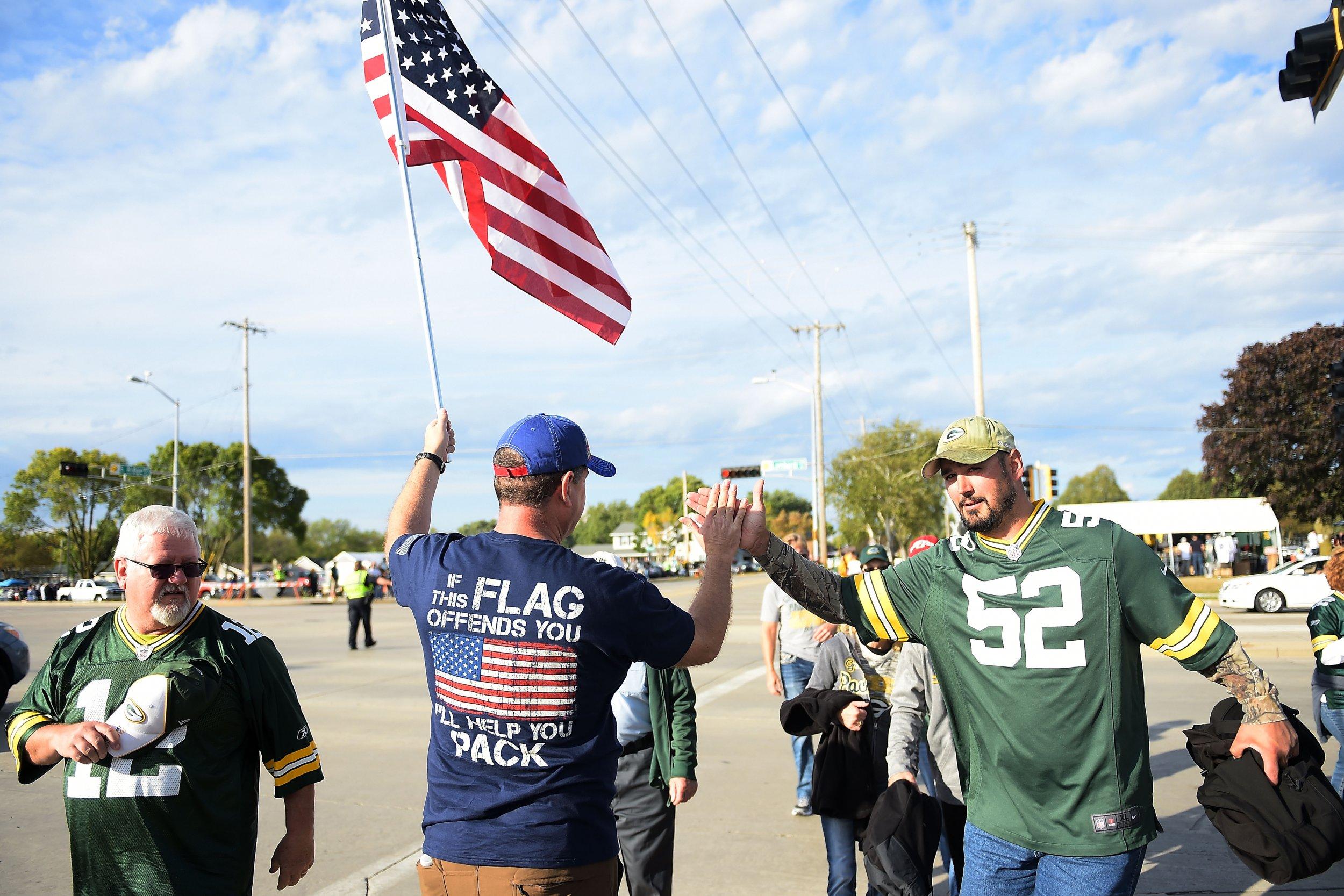 A demonstrator greets fans outside of Lambeau Field in Green Bay, Wisconsin, September 28.