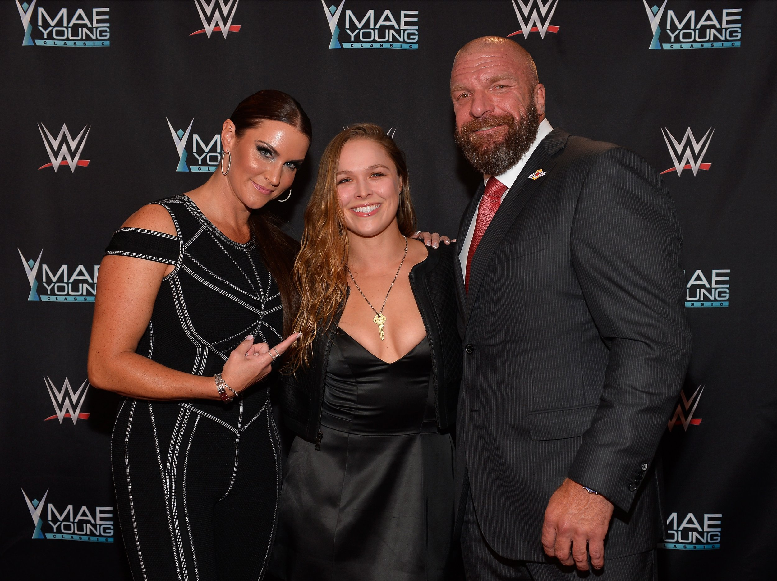 Ronda Rousey, center, with Stephanie McMahon and Triple H.