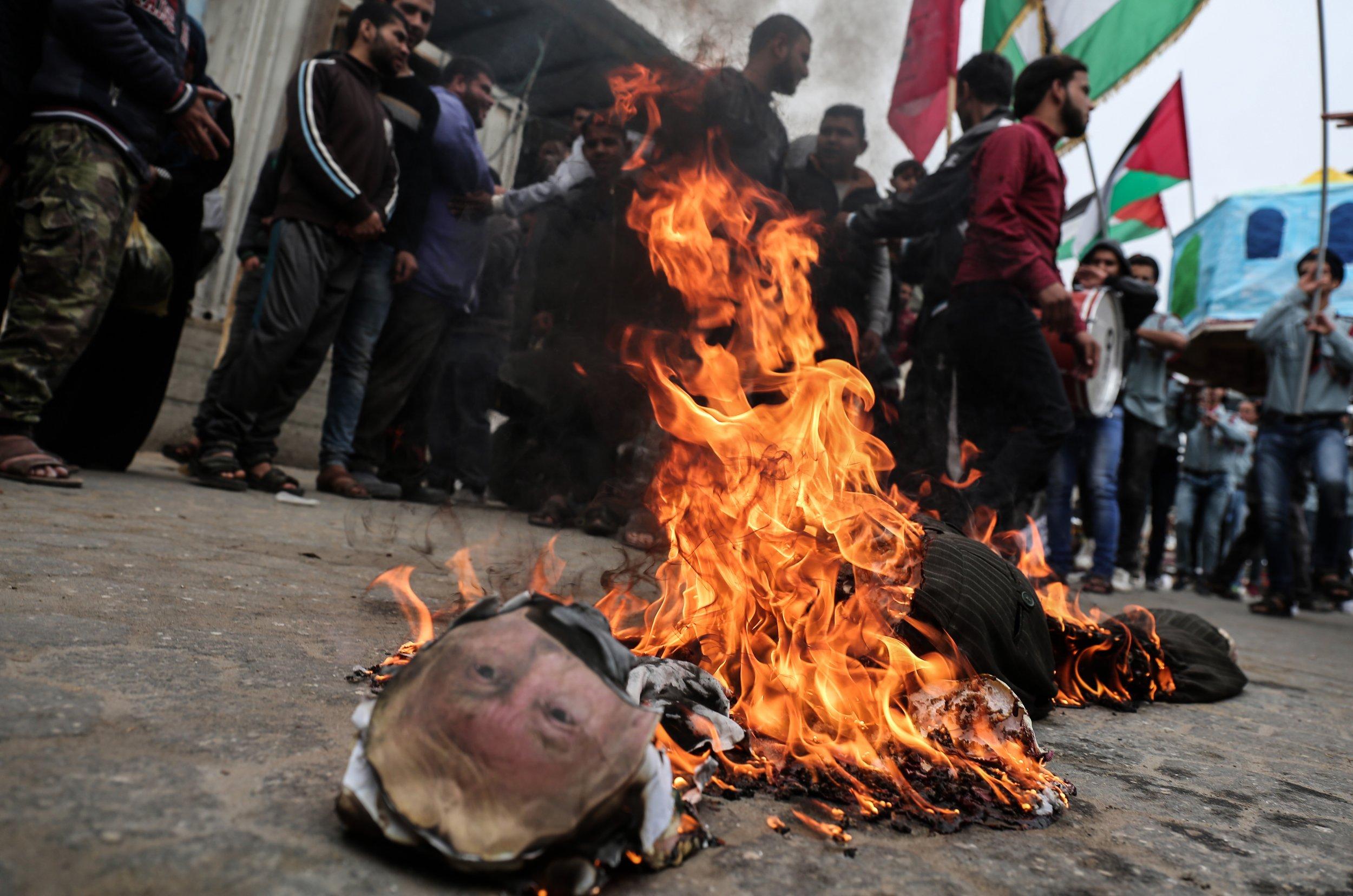 Palestinian demonstrators burn an effigy depicting U.S. President Donald Trump