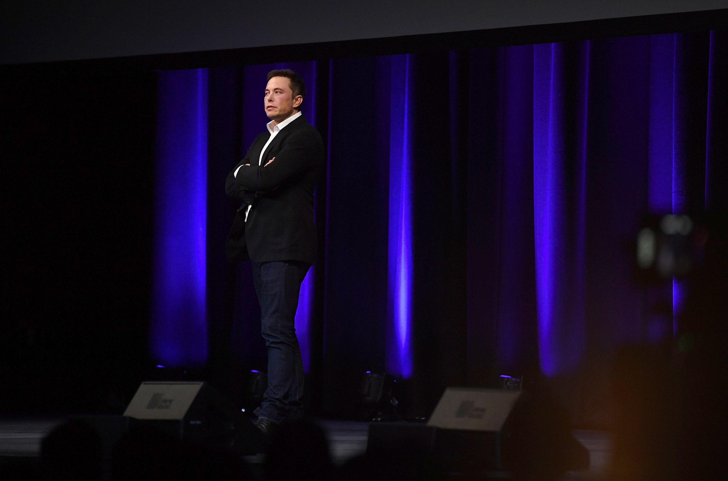 elon musk on stage arms folded